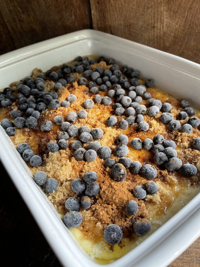 best blueberry coffee cake topped with brown sugar cinnamon and frozen blueberries ready to go into the oven